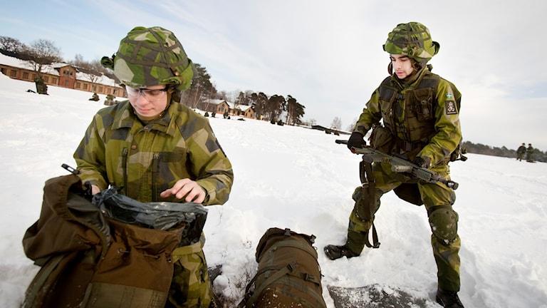 Två värnpliktiga killar packar ihop sin utrustning efter lunchen ute i snön.