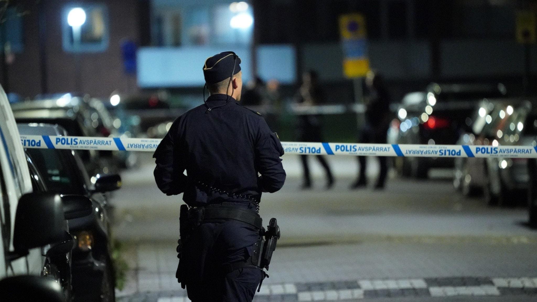 Bilden visar en polis vid ett avspärrat område på natten.