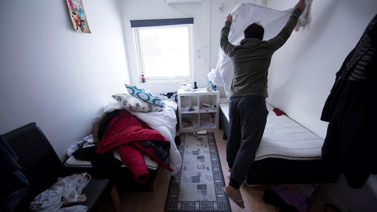 En asylsökande man bäddar sin säng på ett flyktingboende i Pajala.