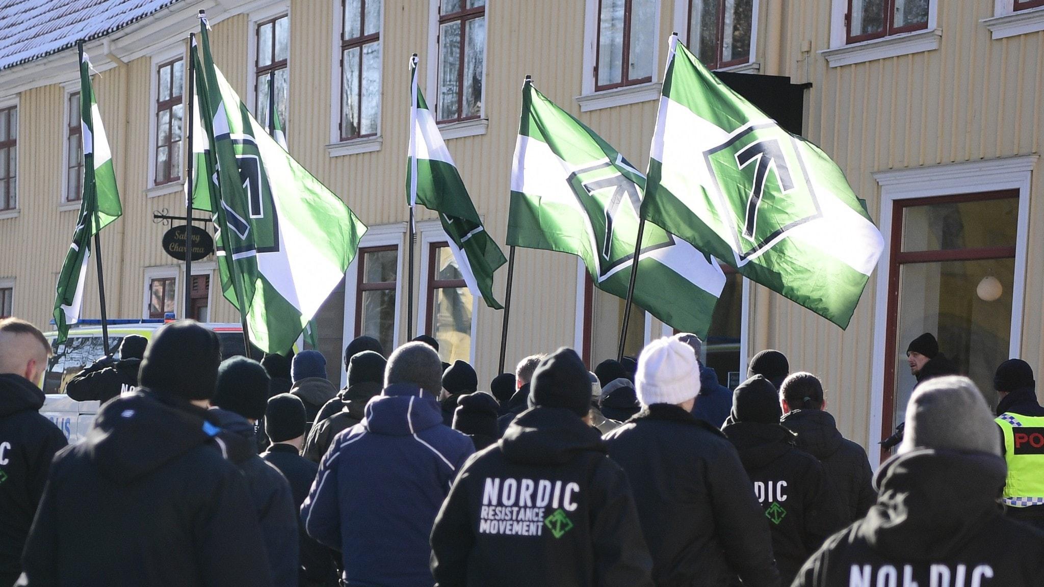 Bild på svartklädda personer med NMR-flaggor som demonstrerar.