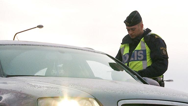 En polis kontrollerar en bilförare.