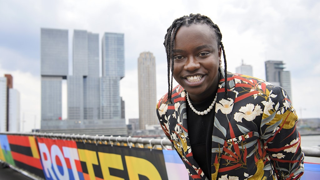 Bild på Tusse som ler och har en blommig kostym på sig. Han står framför skyskrapor i Rotterdam.