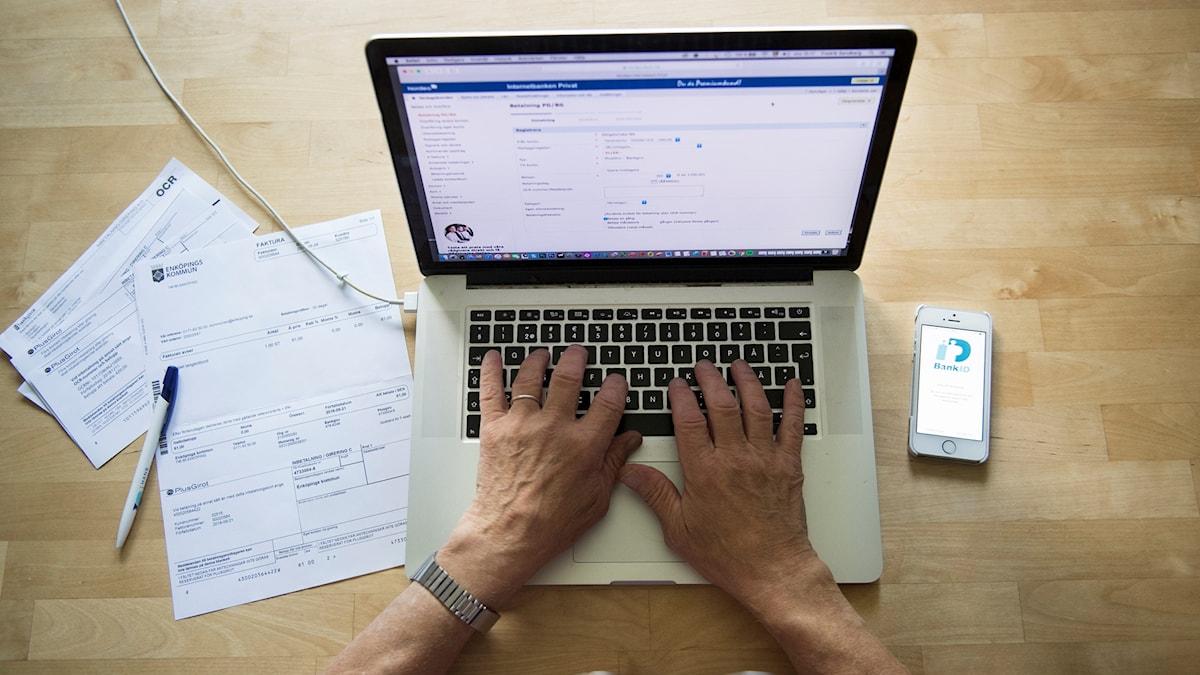 En man betalar räkningar digitalt på nätet med hjälp av bank-id.