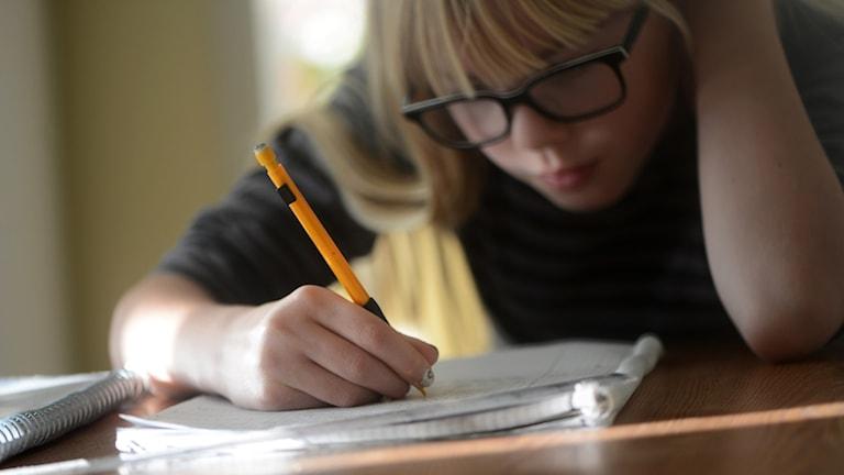 En flicka med glasögon skriver i ett block.