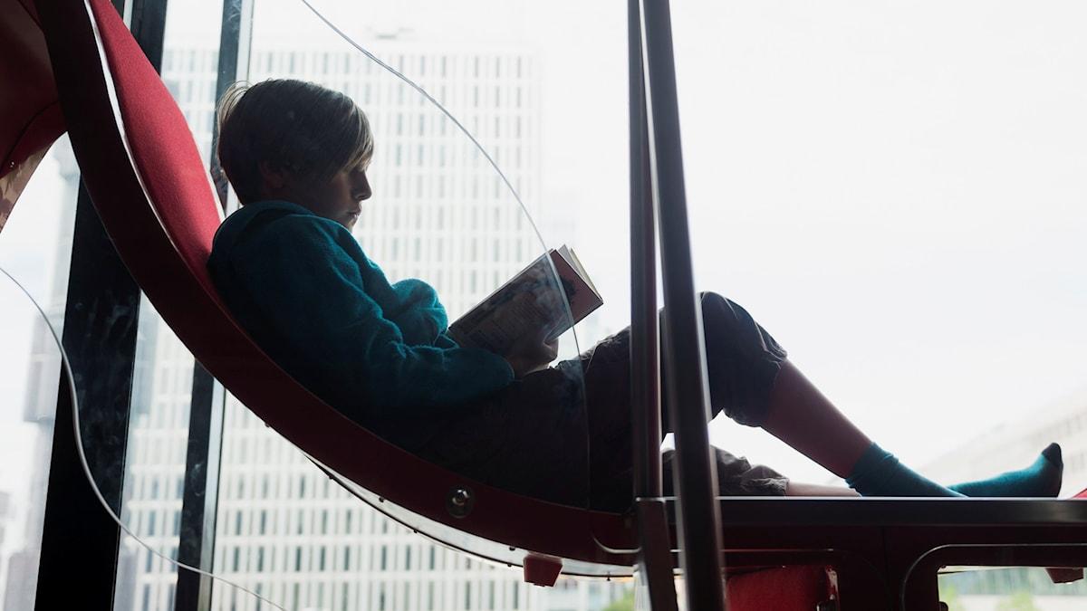 En pojke ligger och läser en bok.