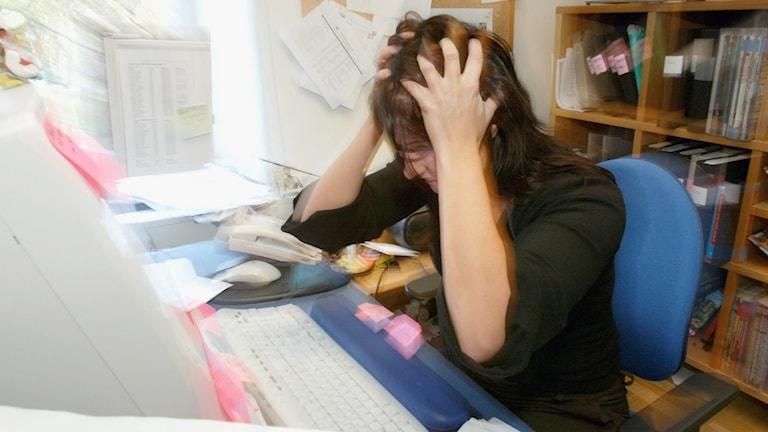 En kvinna framför en dator ser stressad ut.