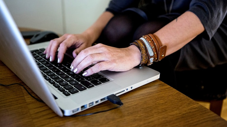 En kvinna skriver på en bärbar dator.