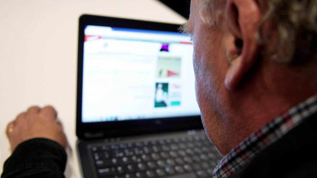 En man surfar på internet på en bärbar dator.