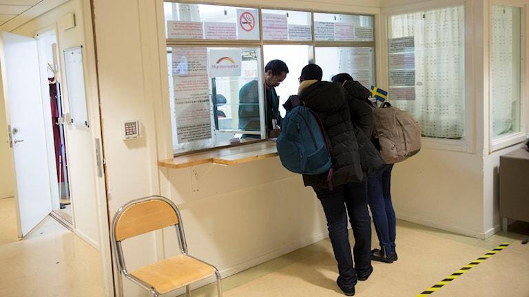 Two people at the reception desk at the Swedish Migration Agency in Märsta. Photo: Maja Suslin / TT.