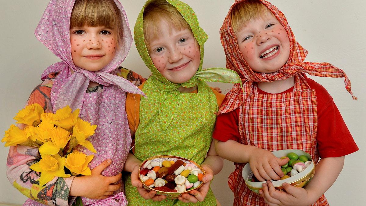 Tre flickor klädda som påskkärringar med påskägg i händerna och stora leenden. Foto: Jonas Ekströmer/TT