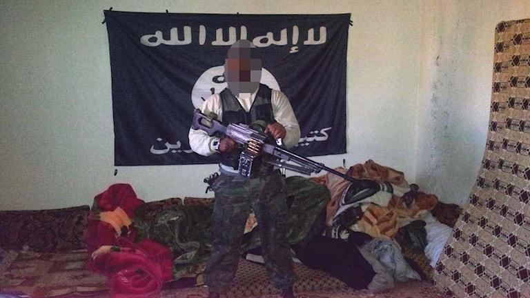 En man som är åtalad för terroristbrott står med ett automatvapen i famnen.