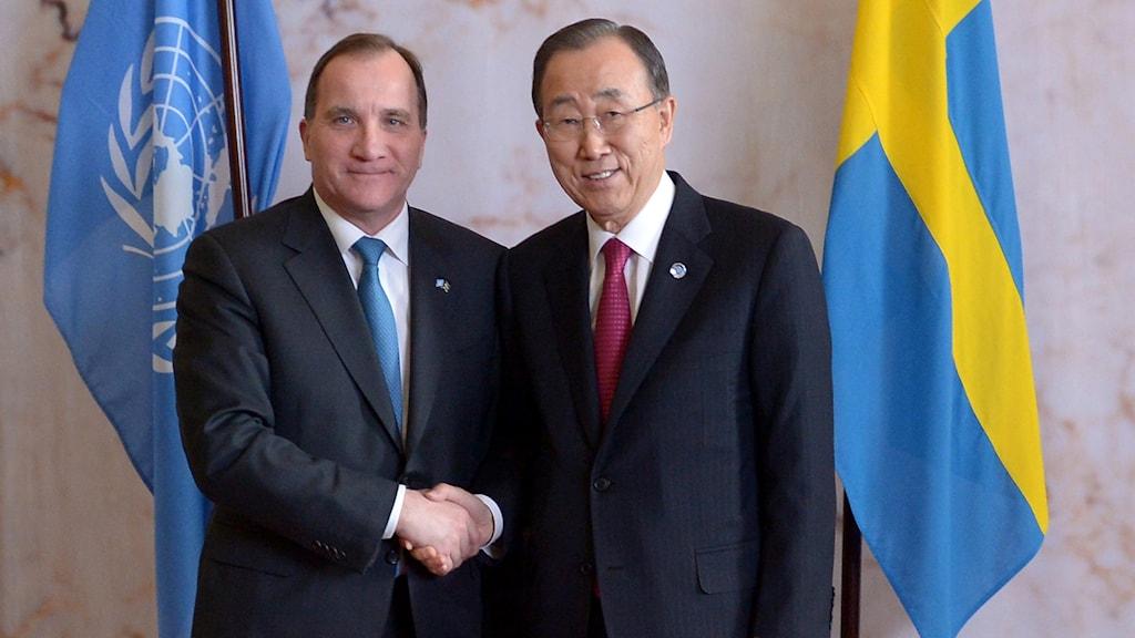 Statsminister Stefan Löfven och FN:s generalsekreterare Ban Ki-Moon tar i hand framför FN:s flagga och Sveriges flagga.