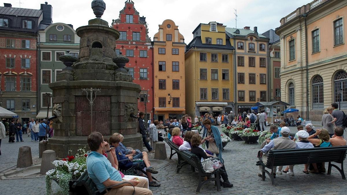 Turister sitter på bänkar på Stortorget i Gamla Stan i Stockholm.