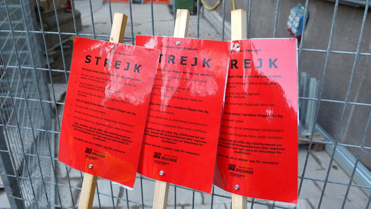"""Tre röda skyltar som det står """"Strejk"""" på, utanför Klara Västra Kyrkogata i Stockholm."""