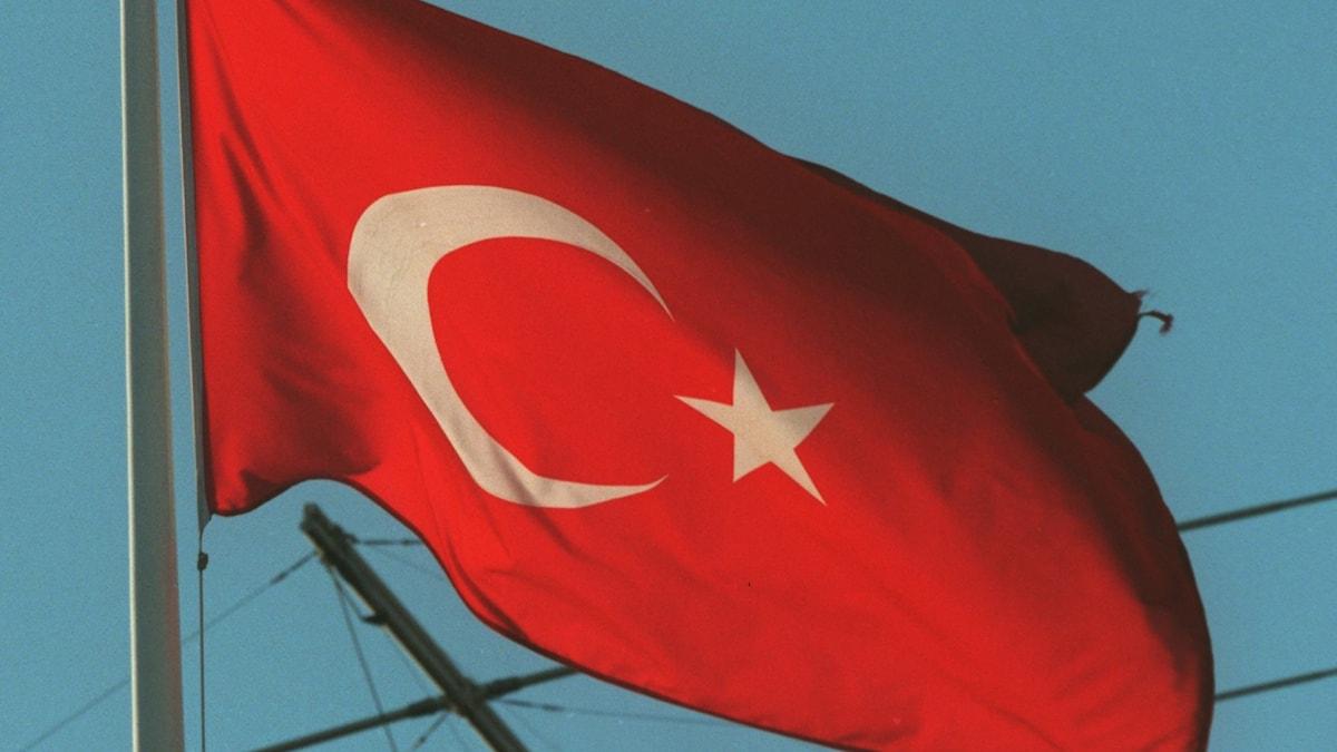 Den turkiska flaggan, med blå himmel i bakgrunden.