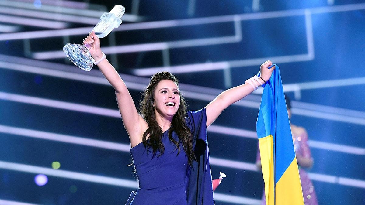 Jamala från Ukraina jublar över vinsten och håller upp en trofé och den ukrainska flaggan.