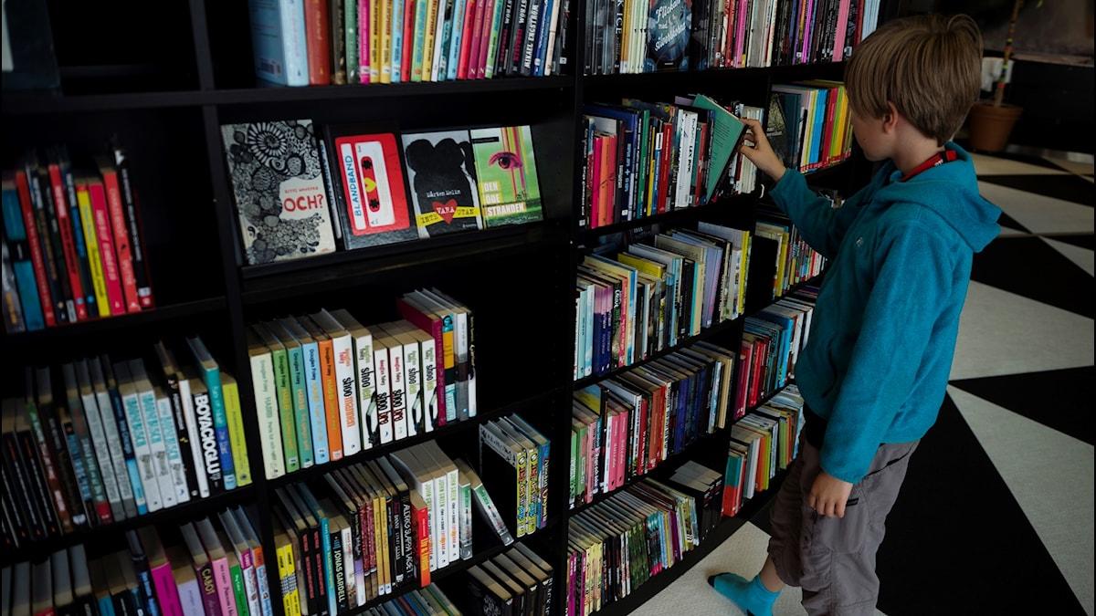 Pojke, 11 år, väljer en bok ur en bokhylla på Kulturhuset i Stockholm.