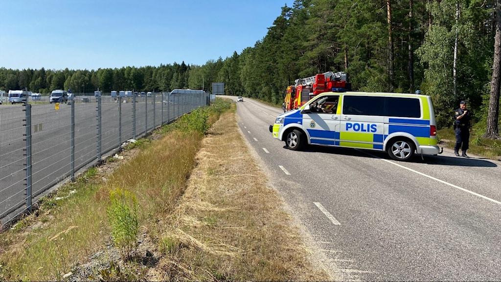 Polisbil och brandbil vid stängsel.