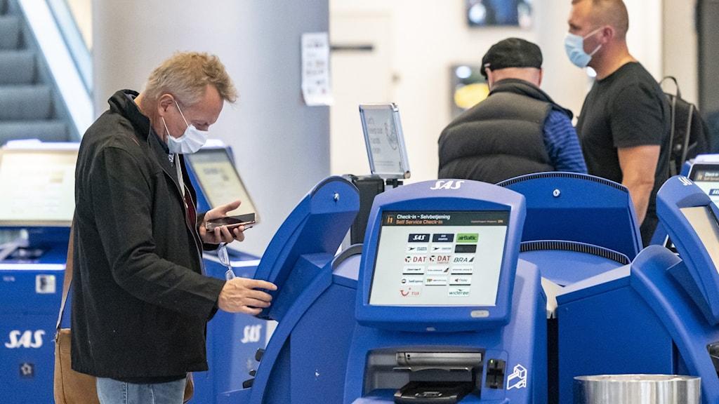 Bilden visar flera personer med munskydd på en flygplats som checkar in till sina flyg.