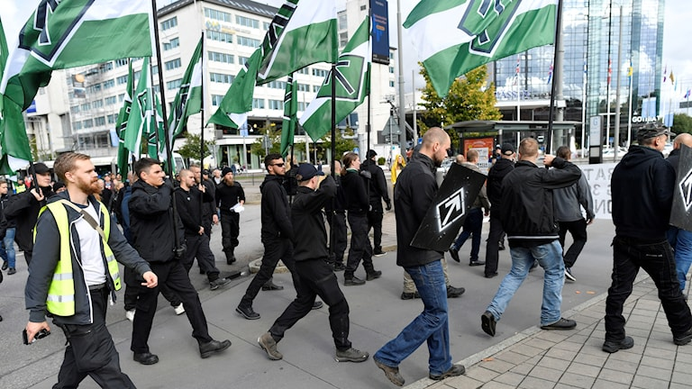 Den nazistiska organisationen Nordiska motståndsrörelsen marscherar med plakat och flaggor i en tillståndslös demonstration i Göteborg.