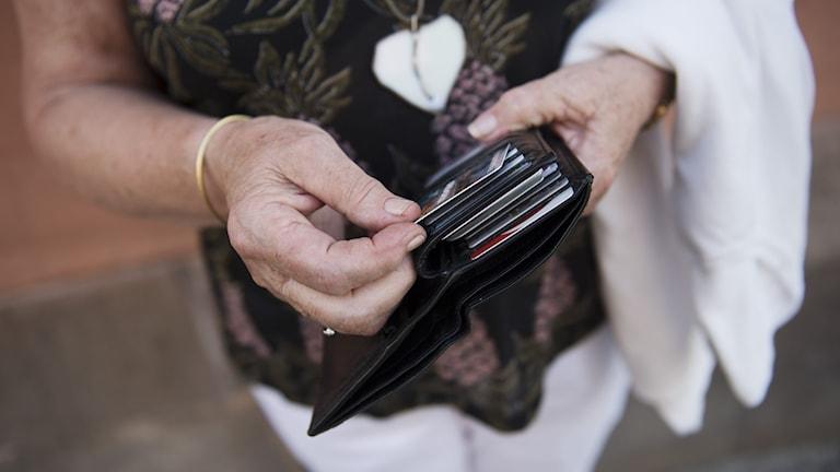 En äldre kvinna håller i en plånbok med bankkort.