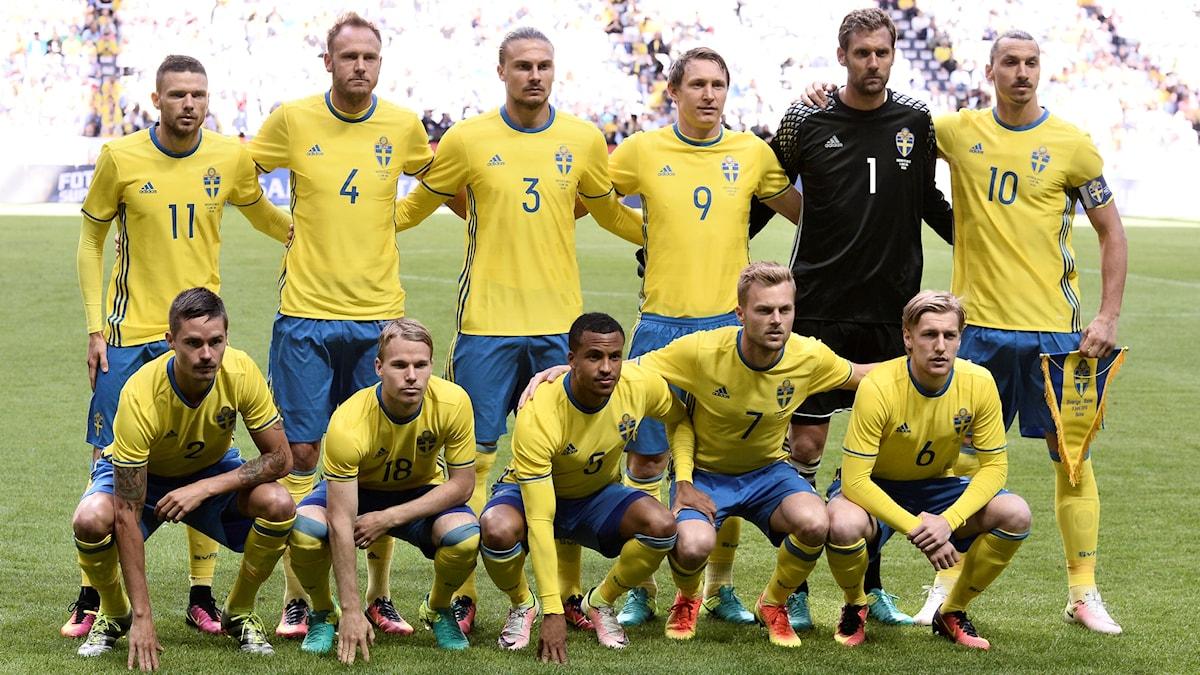 Sveriges landslag i fotboll står uppställda på planen.