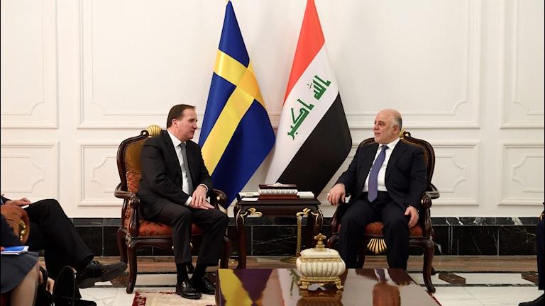 Statsminister Stefan Löfven och Iraks premiärminister Haider al-Abadi sitter under en svensk flagga och en irakisk flagga.
