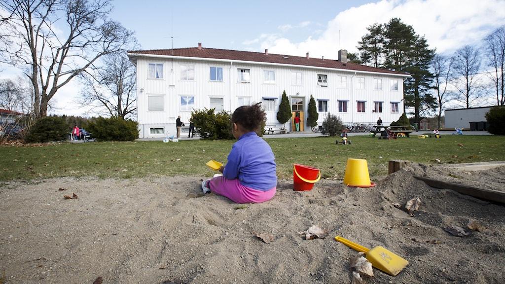 Ett barn sitter i en sandlåda utanför ett asylboende.