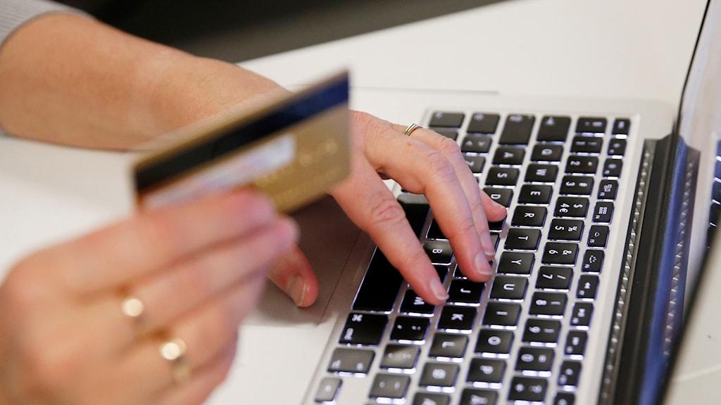 En person handlar på internet med ett bankkort.