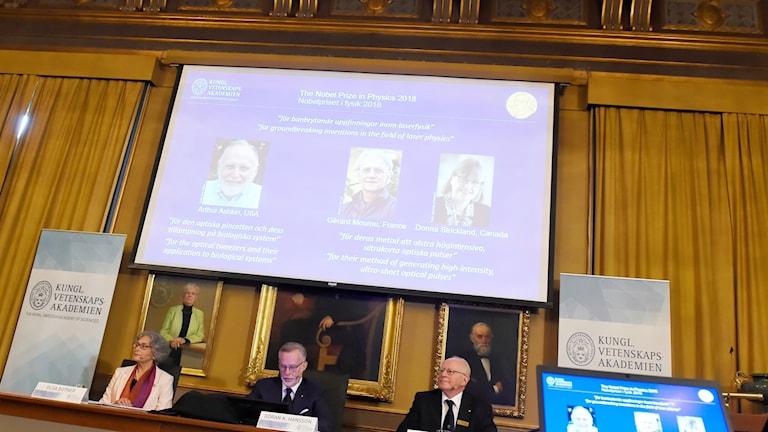 Olga Botner, ordförande för Nobelpriset i fysik, Göran K. Hansson, ständig sekreterare flr Kungliga vetenskapakademien och Mats Larsson, ledamot för Nobelpriset i fysik,  presenterar årets Nobelpristagare i fysik under en pressträff i vid Kungliga Vetenskapsakademien.