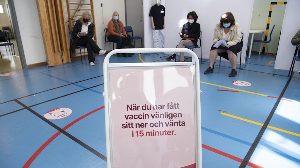 Bilden visar en skylt om vaccinering i en gymnastiksal och människor med munskydd som väntar på vaccin.