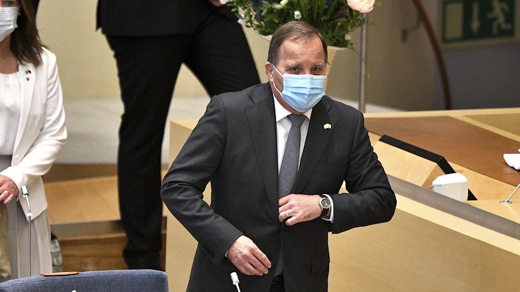 Bild på statsminister Stefan Löfven med munskydd på sig, i riksdagen.