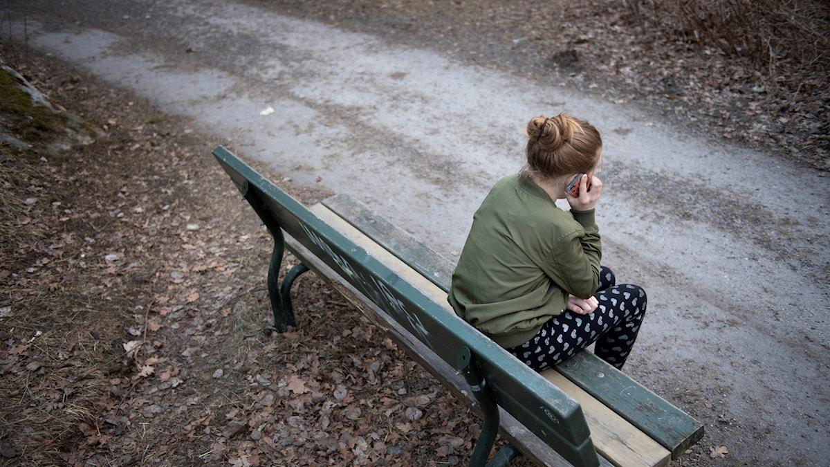 En flicka sitter på en bänk och pratar i en mobiltelefon