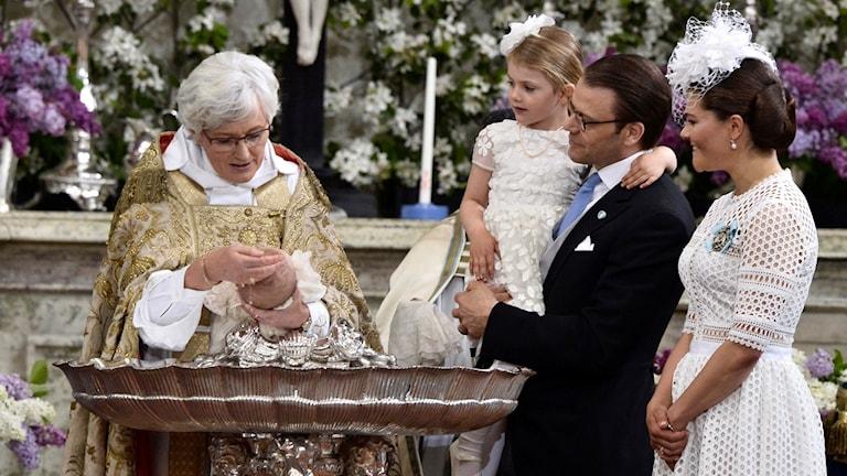 Ärkebiskop Antje Jackelen döper prins Oscar. Prinsessan Victoria, prins Daniel och prinsessan Estelle står bredvid.