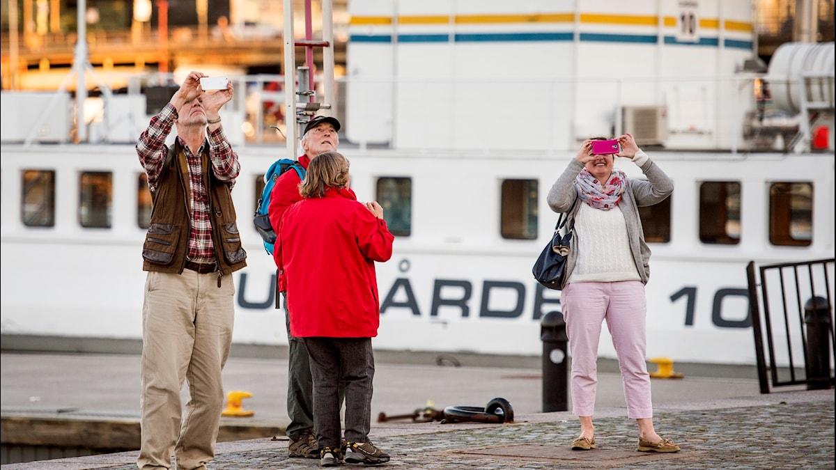 Turister fotograferar med sina smartphones, på Strandvägen i Stockholm.