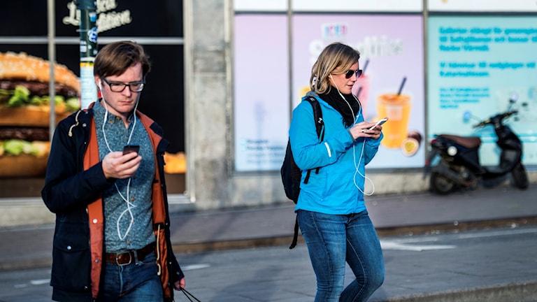 En man och en kvinna går på en gata och tittar ner i sina smarta telefoner.