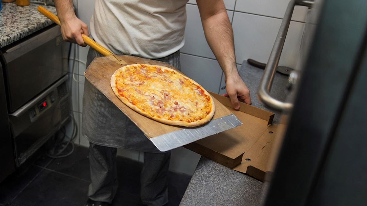 En pizzabagare tar ut en pizza ur ugnen.