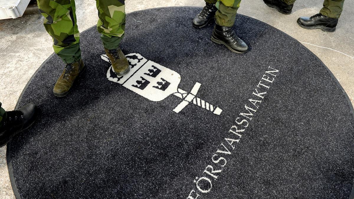 Fötter på soldater på en matta med Försvarsmaktens logga.