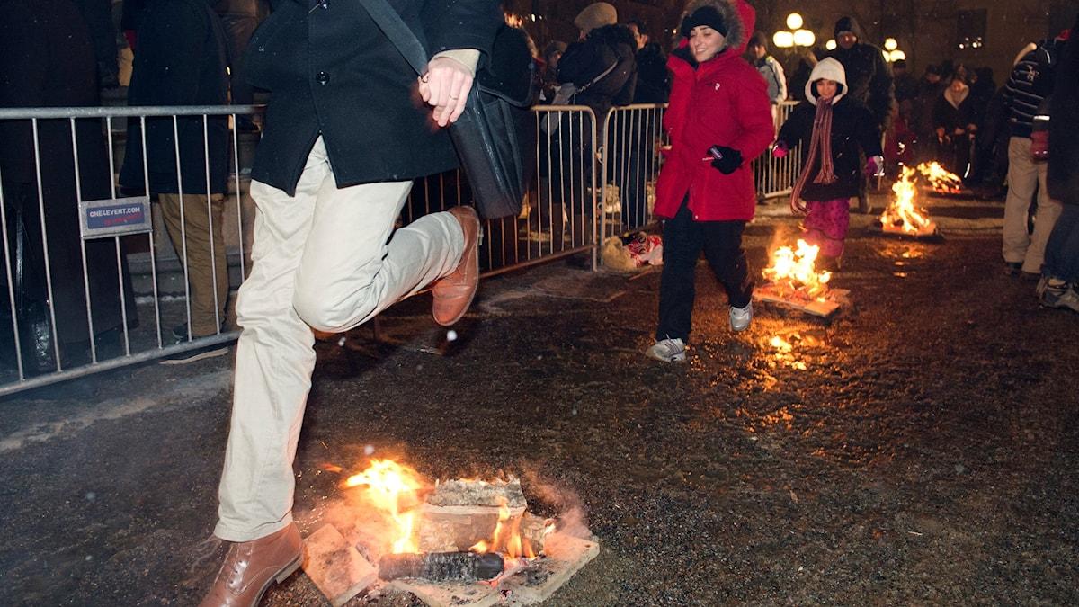 Genom att hoppa över eldar firar människor Eldfesten i Kungsträdgården i Stockholm