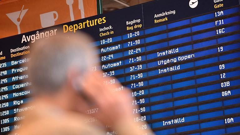 Skärm med avgångstider på Arlanda flygplats. I förgrunden en man som talar i telefon.