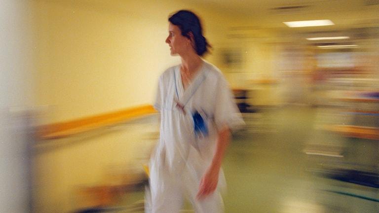 En sjuksköterska skyndar fram i en korridor.