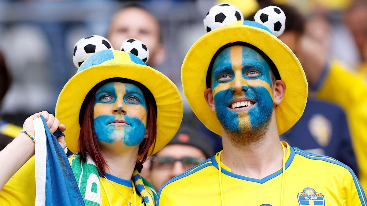 Två svenska fotbolls-supportrar på matchen mellan Sverige och Irland. Deras ansikten är målade som svenska flaggan.