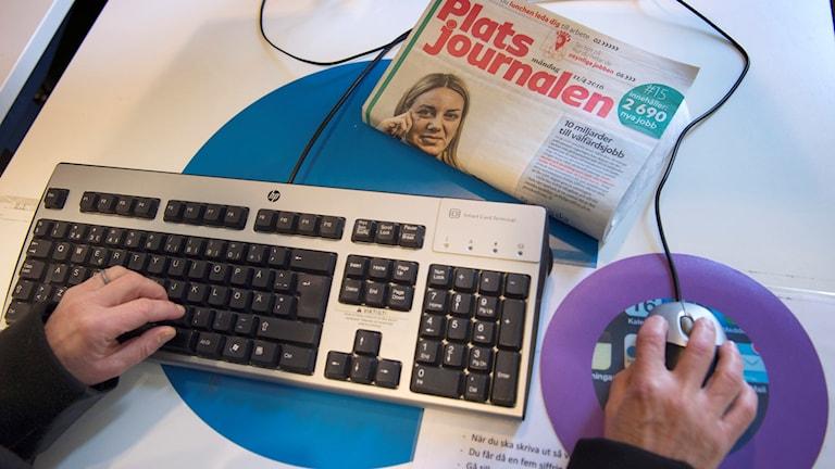 Arbetslös person söker jobb vid dator på Arbetsförmedlingen.