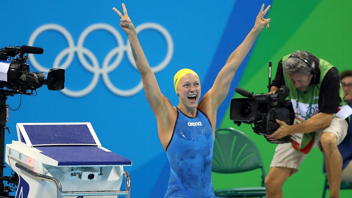 Sarah Sjöström lyfter triumferande armarna i luften efter att ha vunnit guld i hundra meter fjärilsim.