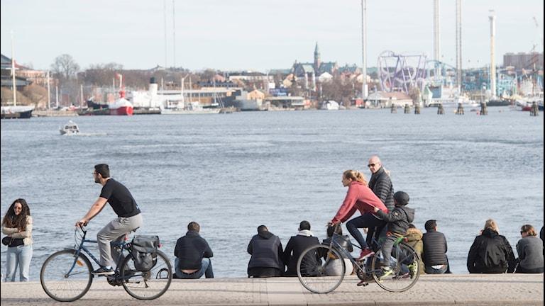 Stockholmare vid Nybrokajen njuter i den 17-gradiga vårsolen.