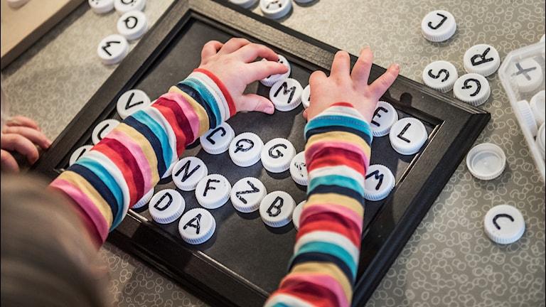 Ett barn på en förskola leker med bokstavsknappar
