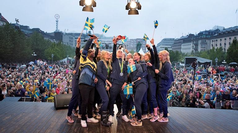 Fotbollsdamerna tar bild på sig själva på scenen där de svenska medaljörerna firas i Kungsträdgården.