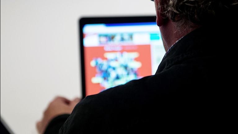 En anonym man surfar på en webbsida.