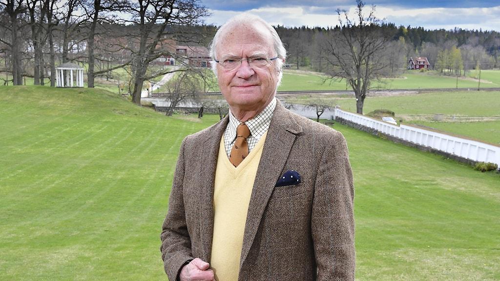 Bild på kungen som står på en gräsmatta utanför Stenhammar slott.