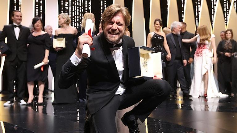 Ruben Östlund poserar glatt på scenen efter att han vunnit Guldpalmen.